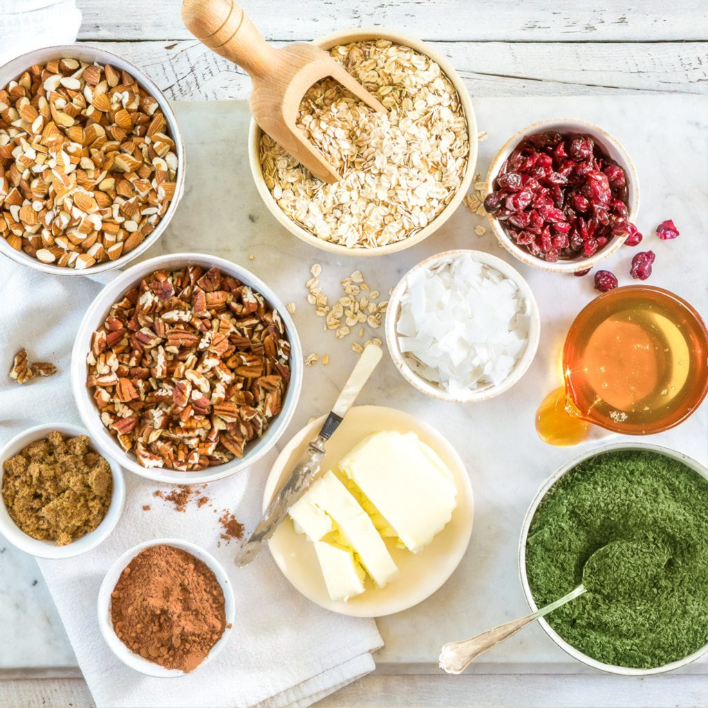 matcha granola ingredients, including rolled oats, cranberries, coconut flakes, pecans, almonds, honey, butter, cinnamon, brown sugar, and matcha powder