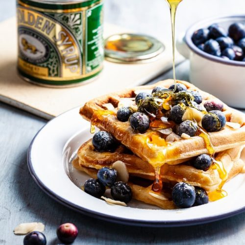 plate of mochi waffles with blueberries and honey golden syrup drizzled with wooden spoon