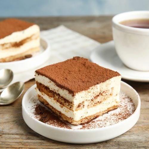espresso tiramisu on a plate with mascarpone custard layer sprinkled with cocoa powder and coffee