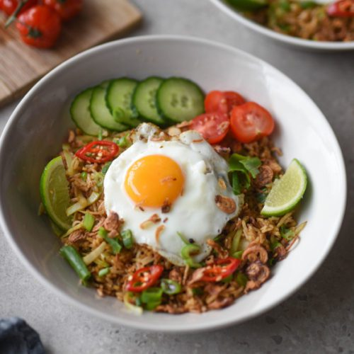 fried rice with egg nasi goreng kampung with tomatoes, chilies, rice, lime in a bowl