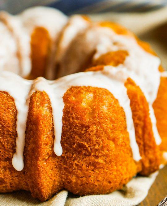 peach Cobbler Pound cake Bundt,Cake,With,White,Glaze,On,Rustic,Background